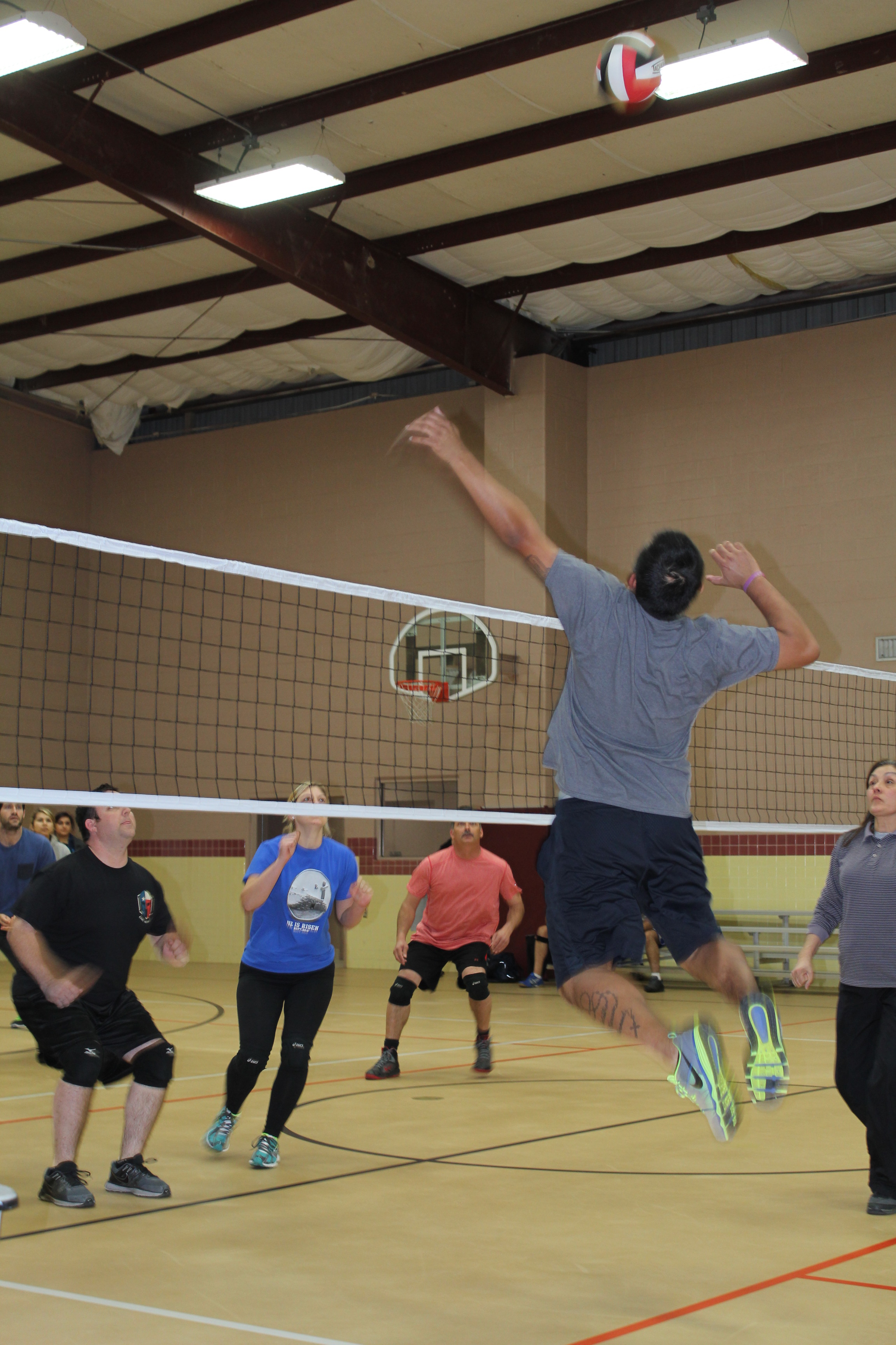 Man jumping in front of volleyball net to hit volleyball in indoor court