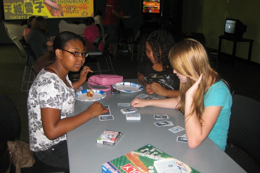 Teen girls sitting at table playing card game